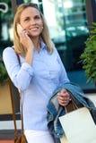 Красивая молодая женщина используя ее мобильный телефон в улице Стоковые Изображения RF