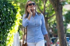 Красивая молодая женщина используя ее мобильный телефон в улице Стоковое Фото