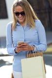 Красивая молодая женщина используя ее мобильный телефон в улице стоковые изображения