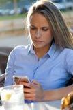 Красивая молодая женщина используя ее мобильный телефон в ter ресторана стоковые фотографии rf