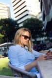 Красивая молодая женщина используя ее мобильный телефон в ter ресторана стоковые фото