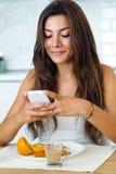 Красивая молодая женщина используя ее мобильный телефон и наслаждающся breakf Стоковое Изображение