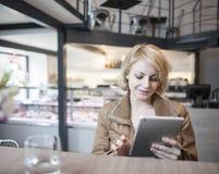 Красивая молодая женщина используя цифровую таблетку в кафе Стоковая Фотография RF