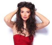 Красивая молодая женщина исправляя ее волосы стоковое изображение rf