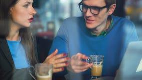 Красивая молодая женщина и человек обсуждая в кафе сток-видео
