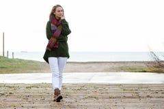 Красивая молодая женщина идя в холодную зиму на пляже Стоковые Фотографии RF