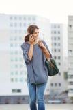 Красивая молодая женщина идя и говоря на сотовом телефоне Стоковое Фото
