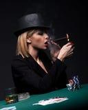 Красивая молодая женщина курит сигару во время игры в покер стоковые изображения rf