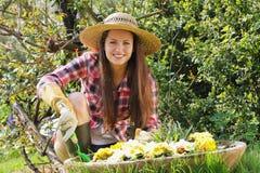 Красивая молодая женщина наслаждаясь ее садом стоковые фото