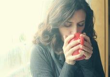 Красивая молодая женщина наслаждаясь чашкой кофе стоковые изображения rf