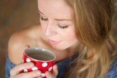 Красивая молодая женщина наслаждаясь чашкой чаю дома Стоковая Фотография