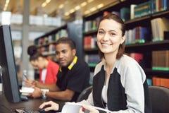 Красивая молодая женщина на библиотеке проводя исследование исследование Стоковая Фотография