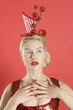 Красивая молодая женщина нося красный headgear над покрашенной предпосылкой стоковые фото