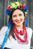 Красивая молодая женщина нося национальный украинский сидеть одежд стоковое фото