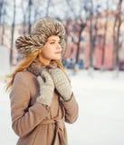 Красивая молодая женщина нося пальто и шляпу над снегом в зимнем дне Стоковые Фото