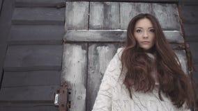 Красивая молодая женщина нося связанный свитер представляя сараем с инструментами видеоматериал