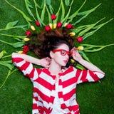 Красивая молодая женщина около желтых и красных тюльпанов лежа на w Стоковое фото RF