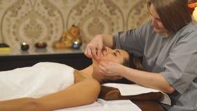 Красивая молодая женщина получая лицевой массаж с закрытыми глазами сток-видео