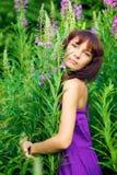 Красивая молодая женщина представляя в зеленой траве стоковое изображение