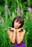 Красивая молодая женщина представляя в зеленой траве стоковая фотография