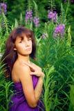 Красивая молодая женщина представляя в зеленой траве стоковые фото