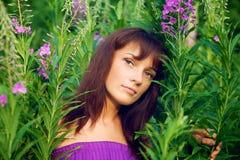 Красивая молодая женщина представляя в траве стоковая фотография