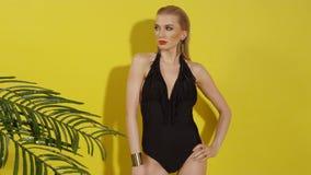 Красивая молодая женщина представляя в черном купальнике над желтой предпосылкой видеоматериал