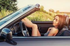 Красивая молодая женщина представляя около автомобиля на дороге Стоковое фото RF