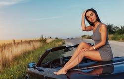 Красивая молодая женщина представляя около автомобиля на дороге стоковые фото