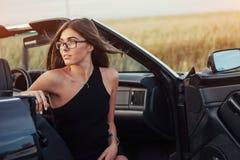Красивая молодая женщина представляя около автомобиля на дороге Стоковые Изображения RF