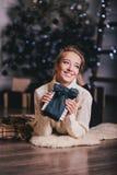 Красивая молодая женщина представляя под рождественской елкой в интерьере праздника Стоковые Изображения