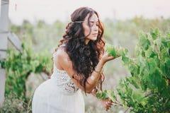 Красивая молодая женщина при длинное вьющиеся волосы одетое в платье стиля boho представляя в поле с одуванчиками стоковые изображения rf