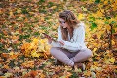 Красивая молодая женщина при таблетка сидя в парке осени Стоковые Фото