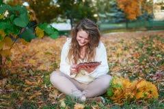 Красивая молодая женщина при таблетка сидя в парке осени Стоковые Изображения