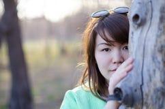 Красивая молодая женщина пряча за деревом Стоковое Изображение