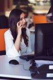 Красивая молодая женщина работая на компьютере и говоря на телефоне стоковые изображения