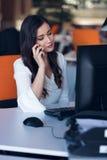 Красивая молодая женщина работая на компьютере и говоря на телефоне стоковая фотография
