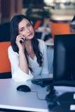 Красивая молодая женщина работая на компьютере и говоря на телефоне стоковое изображение