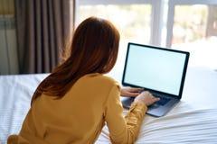 Красивая молодая женщина работая на компьютере дома Стоковые Фотографии RF