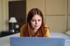 Красивая молодая женщина работая на компьютере дома Стоковая Фотография RF