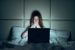 Красивая молодая женщина работая на компьютере дома Стоковые Фото