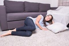 Красивая молодая женщина расслабляющая на ковре дома Стоковое Изображение