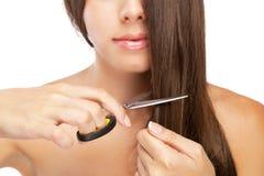 Красивая молодая женщина режа ее волосы стоковое фото rf