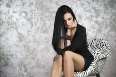 Красивая молодая женщина сидя в кресле Черные платье, ботинки и чулки Стоковое Изображение RF
