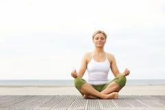 Красивая молодая женщина сидя в представлении йоги на пляже Стоковые Изображения RF