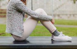 Красивая молодая женщина сидя на скамейке в парке Стоковая Фотография