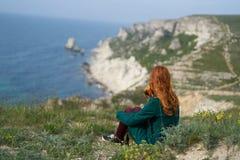 Красивая молодая женщина сидя на скале на горе над морем стоковые изображения