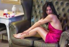 Красивая молодая женщина сидя на софе стоковые фотографии rf