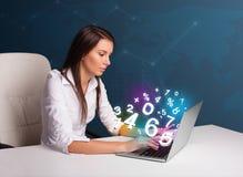 Красивая молодая женщина сидя на столе и печатая на компьтер-книжке с Стоковое фото RF