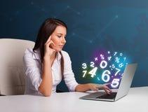 Красивая молодая женщина сидя на столе и печатая на компьтер-книжке с Стоковые Фотографии RF